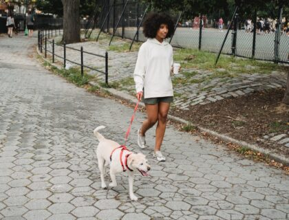 black woman having coffee and walking with purebred dog